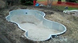 An empty vinyl liner pool under construction by Legendary Escapes