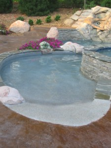 Beach entry on a custom gunite swimming pool built by Legendary Escapes in Highland, Michigan