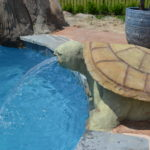 Carved concrete turtle by Karen of Legendary Escapes creates a fountain into the vinyl liner swimming pool with a reef liner.